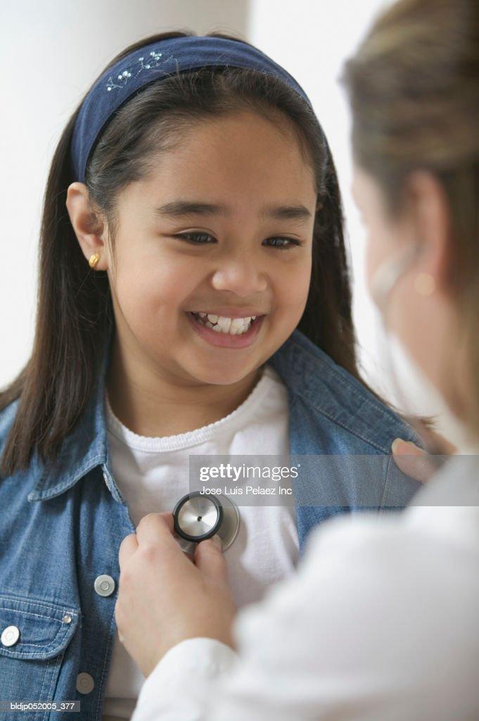 Female doctor examining a girl : Stock Photo