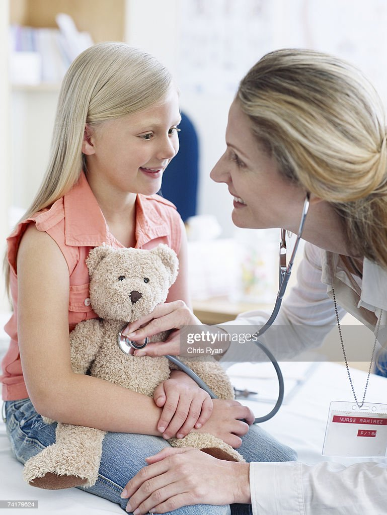 Female doctor examining girl with teddy bear : Stock Photo