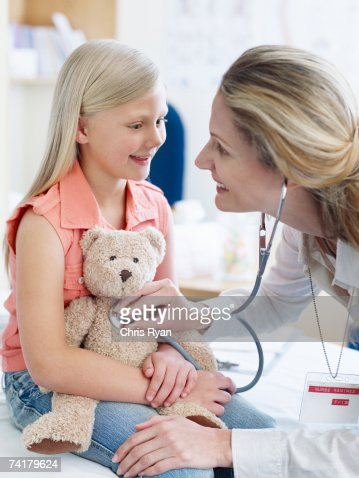 Female doctor examining girl with teddy bear : Stock Photo