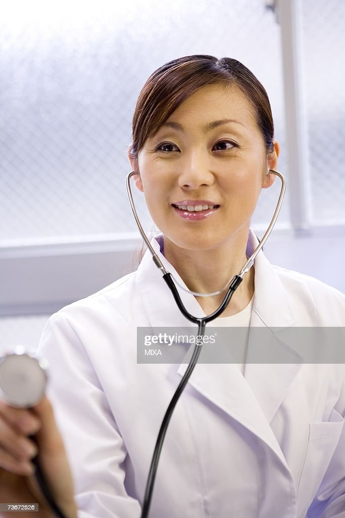 A female doctor examining patient with stethoscope : Stock Photo