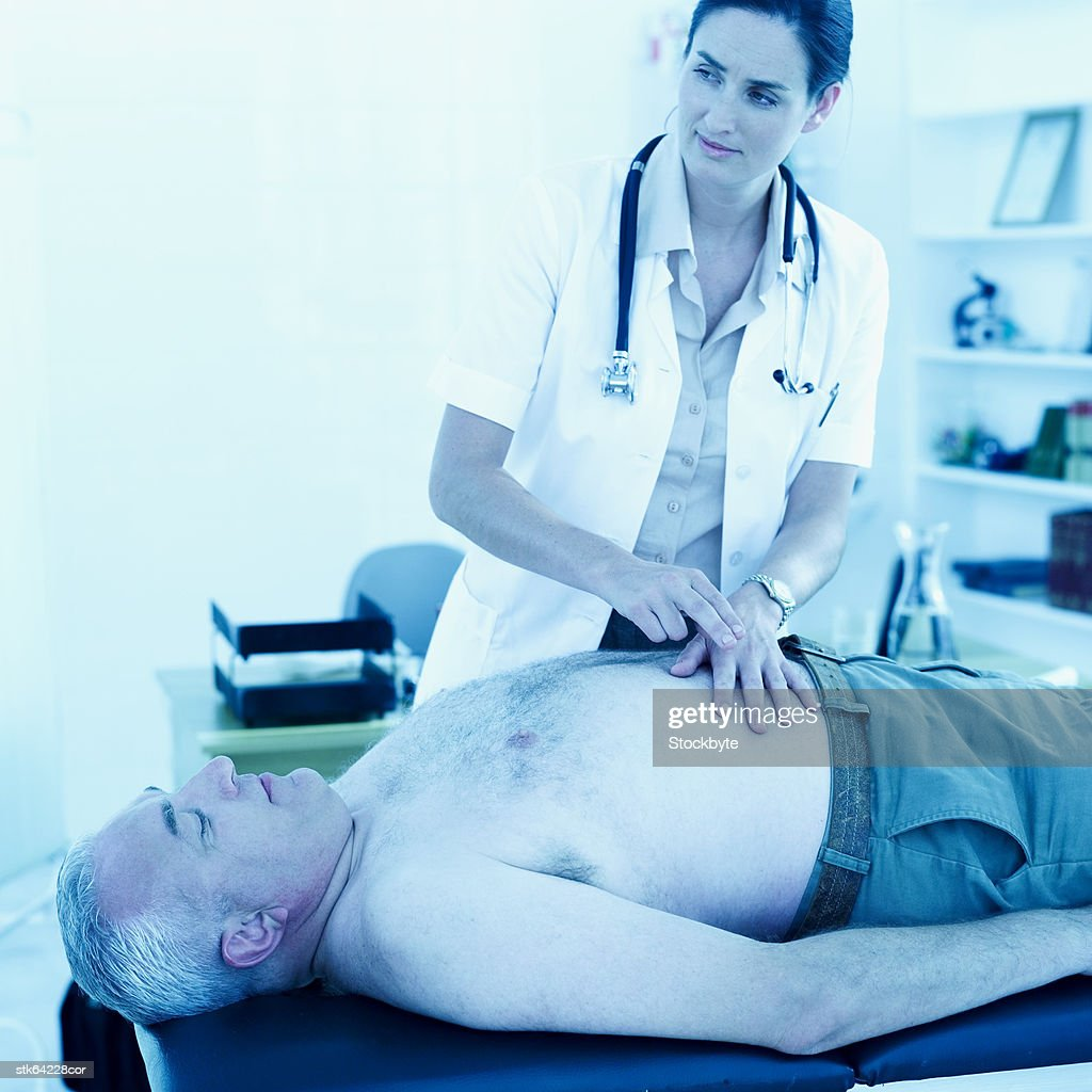 female doctor examining the belly of an elderly man