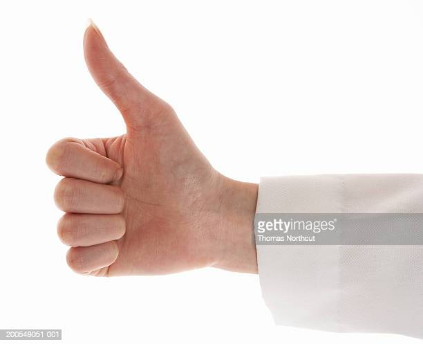 Female doctor giving thumbs up sign, close-up of hand