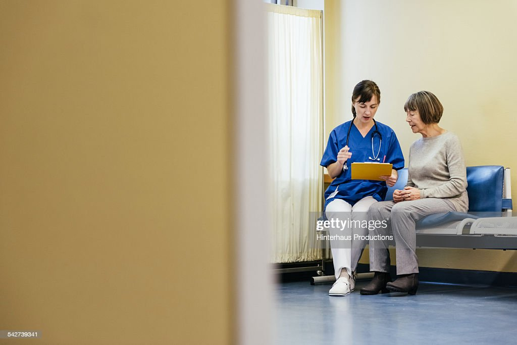 Female Doctor Help Senior Patient With Paperwork