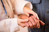 Caring female doctor helping senior male patient.  She checks his hands for arthritis, aids him in walking, or just consoles him. Close up of hands. Unrecognizable people. Nursing home/assisted living
