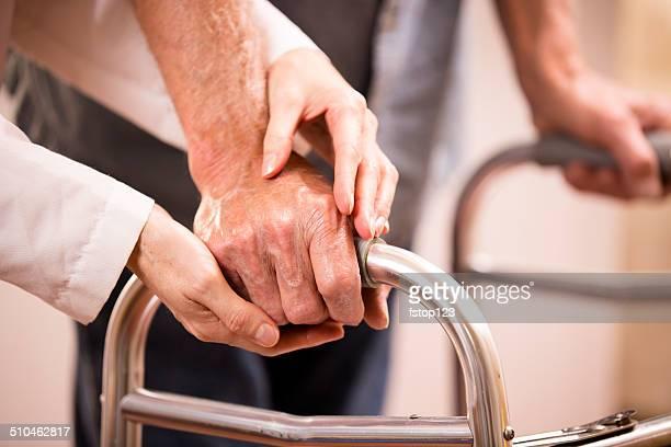 Doctora ayuda hombre senior paciente uso walker.  Agarrar de la mano.