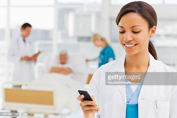 Female doctor holding cellphone