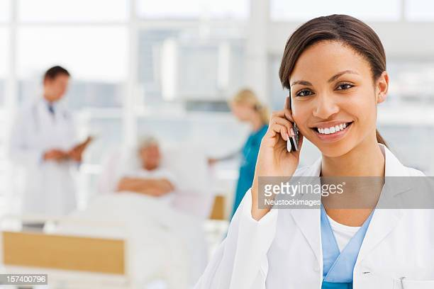 Female doctor holding cellphone with colleagues and patient in background