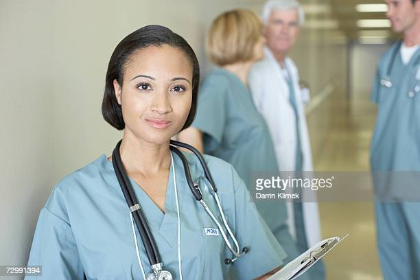 'Female doctor holding clipboard, doctors having discussion in background'