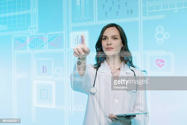 Female doctor holding digital tablet, touching graphical screen