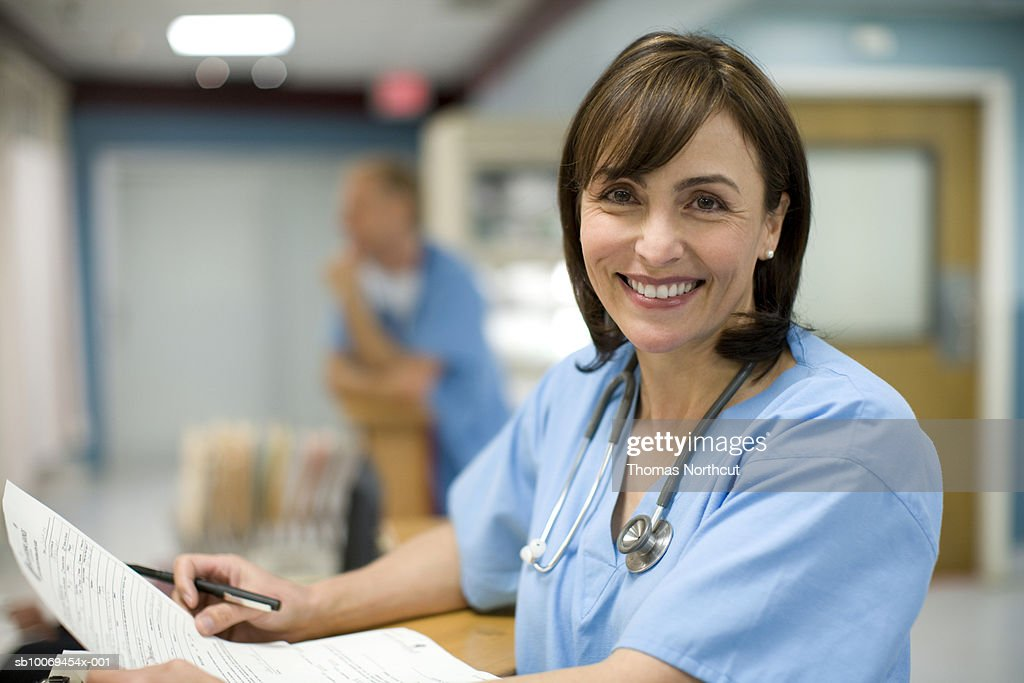 Female doctor holding medical records, smiling, portrait : Stock Photo