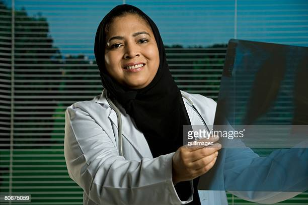 Female doctor holding X-ray, smiling, portrait