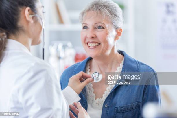 Female doctor listens to senior woman's heartbeat