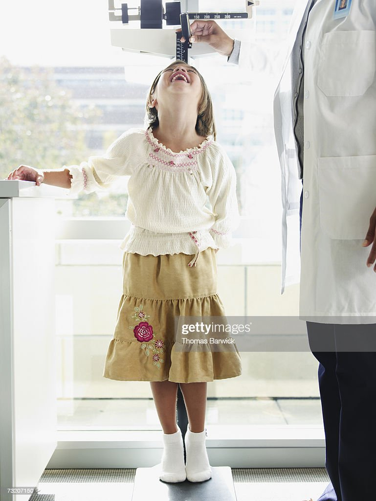 Female doctor measuring girl's (10-11) height in exam room : Stock Photo