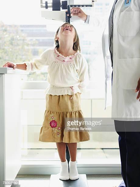 Female doctor measuring girl's (10-11) height in exam room