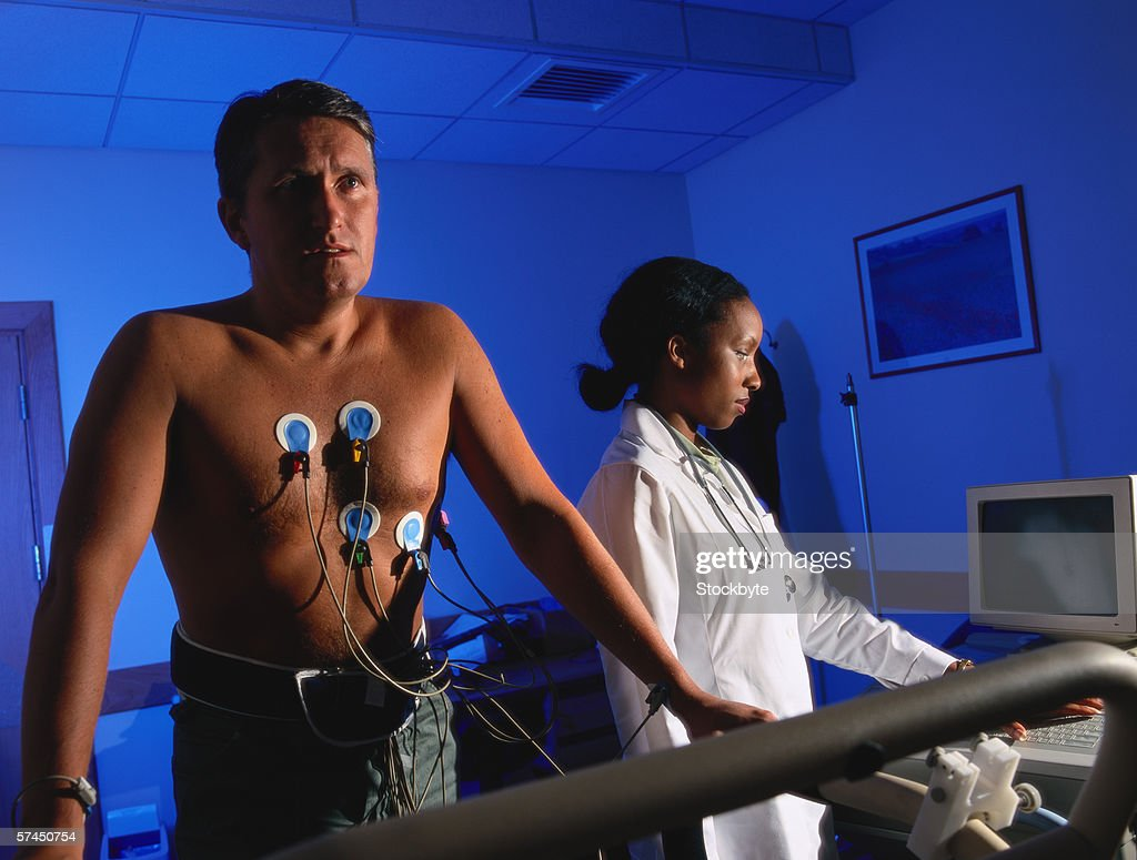A female doctor performing a stress test on a man : Stock Photo