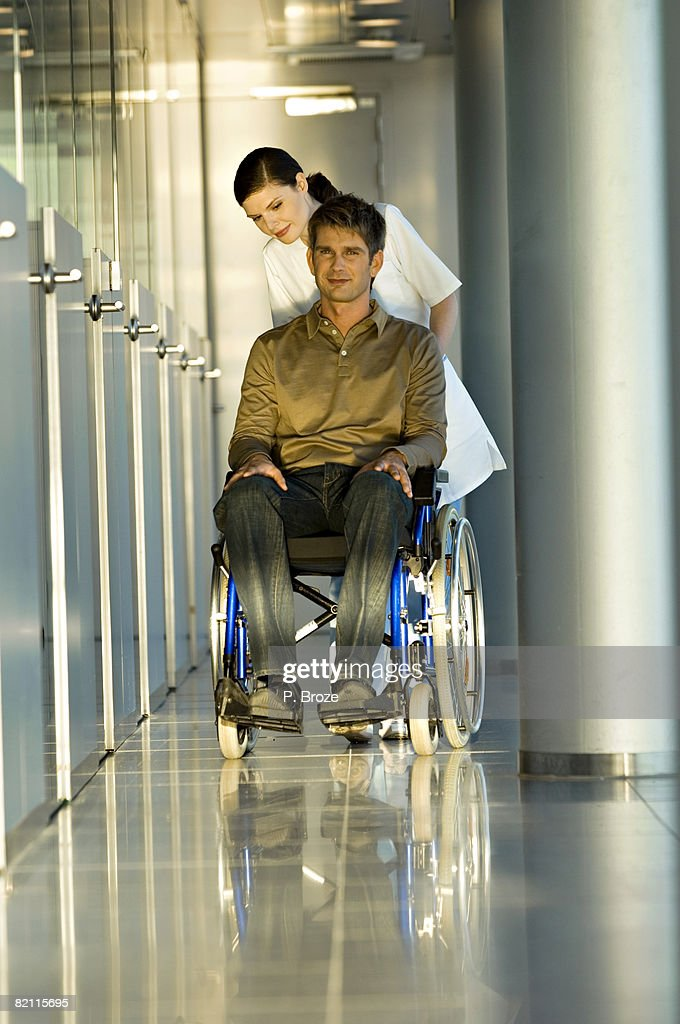 Female doctor pushing a male patient sitting in a wheelchair : Stock Photo