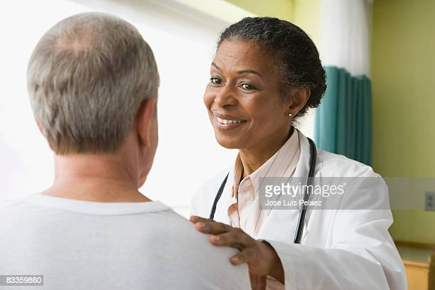 Female doctor putting hand on male patient