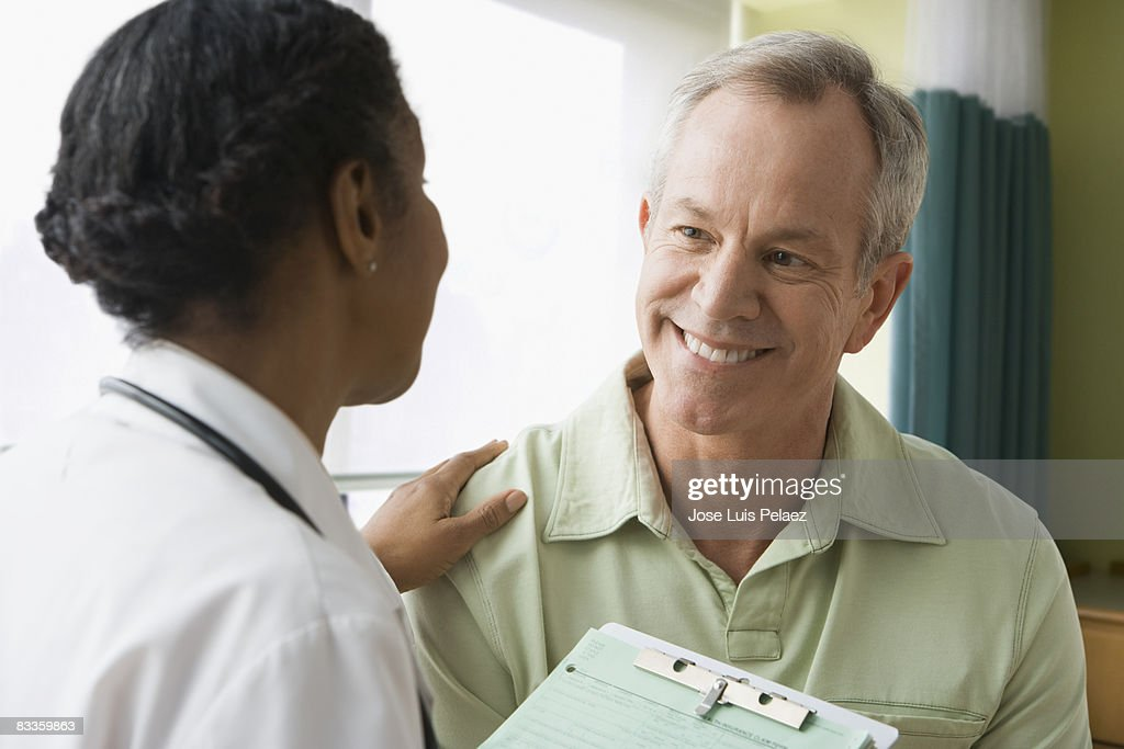 Female doctor putting hand on male patient : Stock Photo