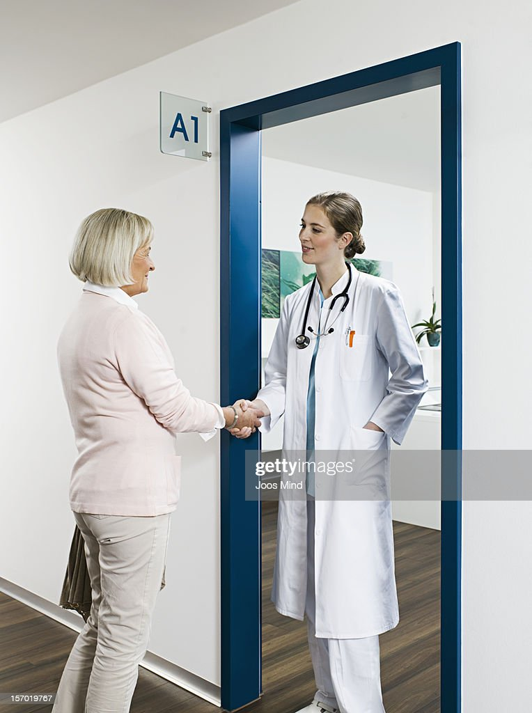 female doctor shaking patient hand, smiling : Stock Photo
