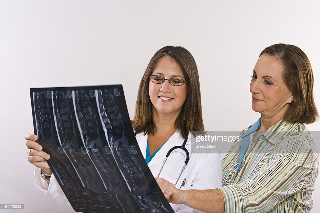 Female doctor showing an MRI scan to patient : Stock Photo