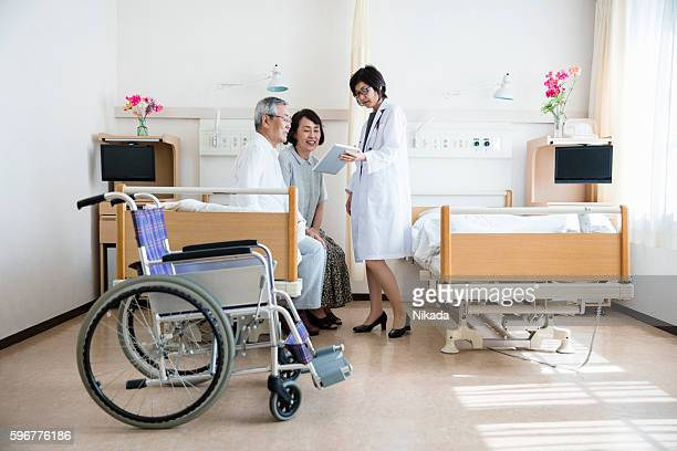Female doctor showing digital tablet to senior couple
