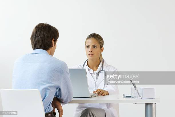 Female doctor sitting across from male patient at desk, using laptop computer