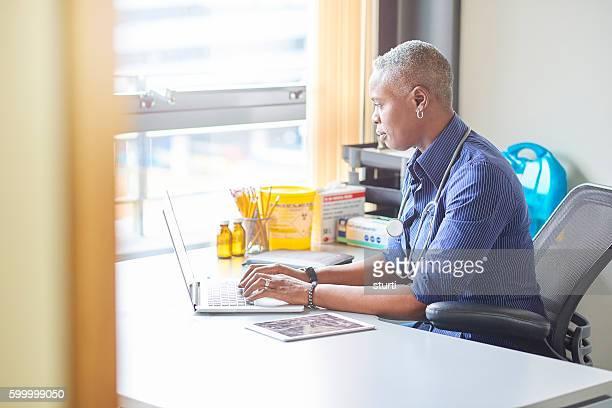Weiblich Arzt sitzen an Ihrem Schreibtisch