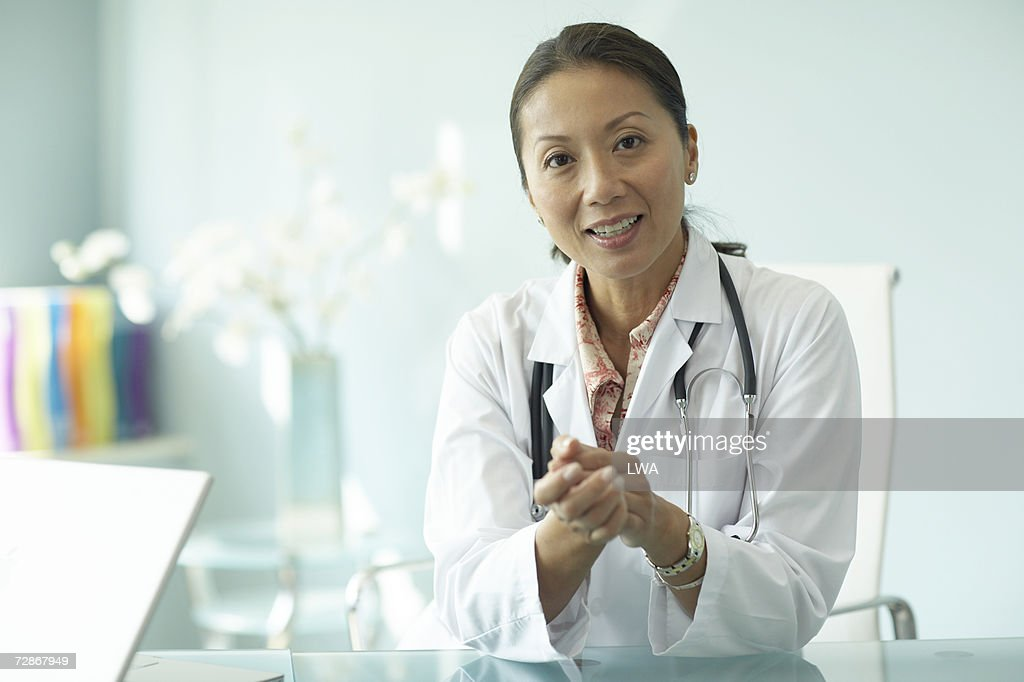Female doctor sitting at table, smiling, portrait : Stock Photo