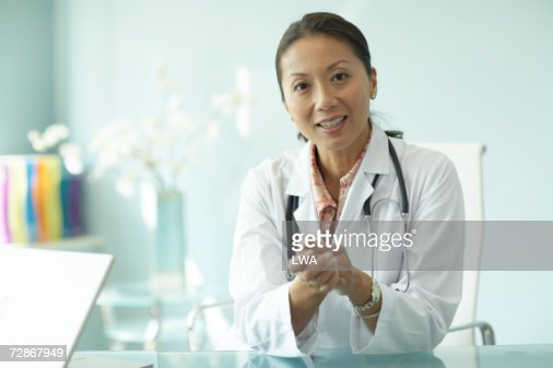 Female doctor sitting at table, smiling, portrait : Stockfoto