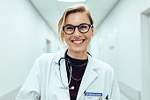 Portrait of happy young female doctor standing in hospital corridor. Caucasian woman working in healthcare center.