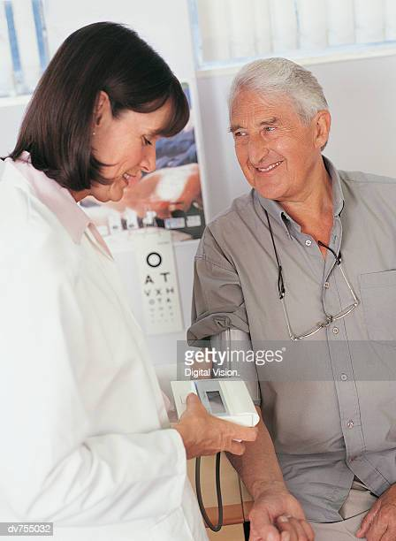 Female Doctor Taking Male Patient's Blood Pressure