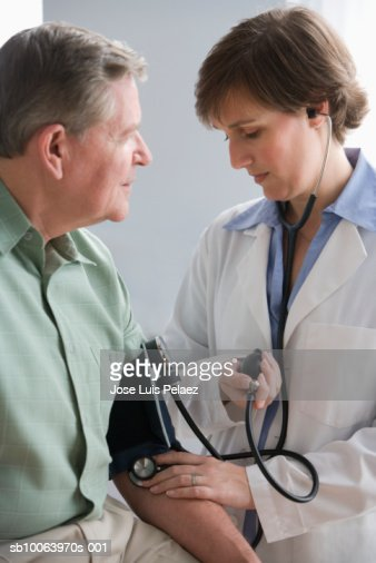 Female doctor taking male patient's blood pressure : Stock Photo