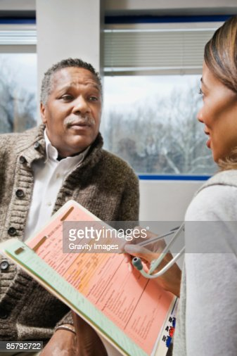 Female doctor taking notes from patient : Stock Photo