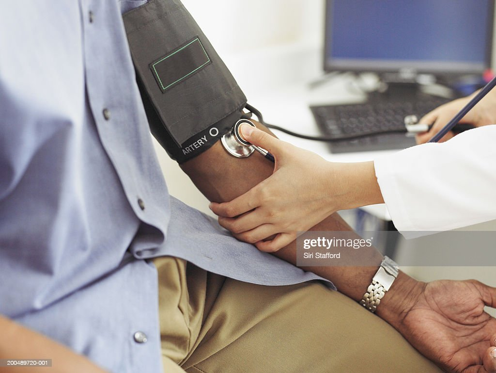Female doctor taking patient's blood pressure