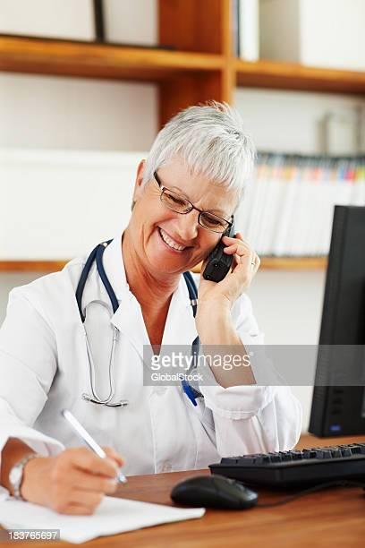 Ärztin sprechen auf ein schnurloses Telefon