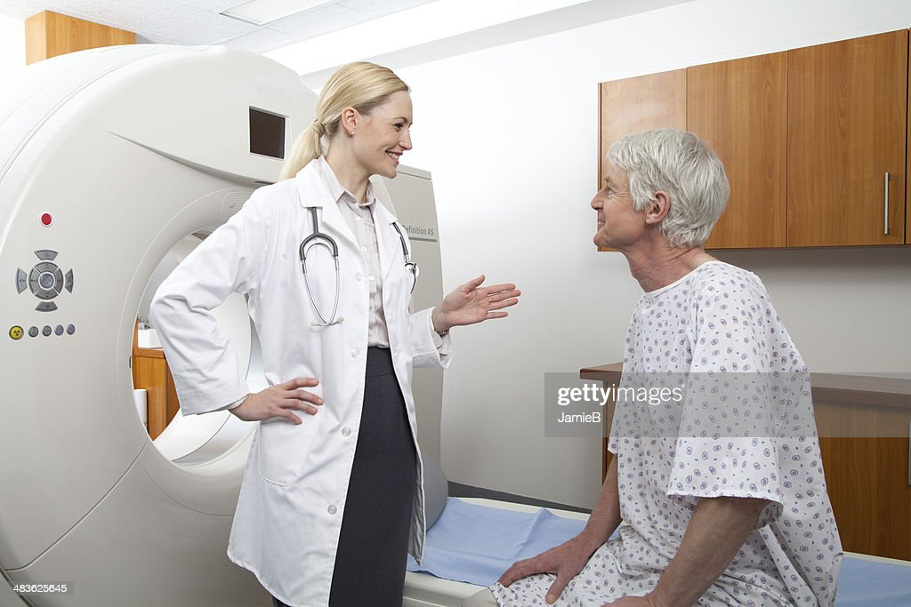 Female doctor talking to male patient next to medical scanner : Stock Photo