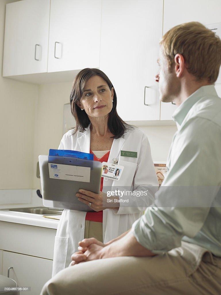 Female doctor talking to male patient : Stock Photo