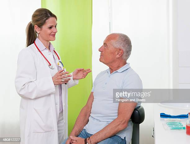 Female doctor talking to senior male patient