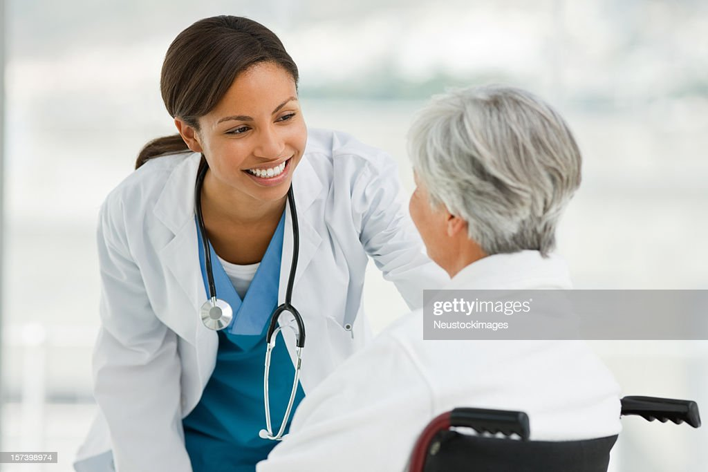 Female doctor talking with senior patient : Stock Photo