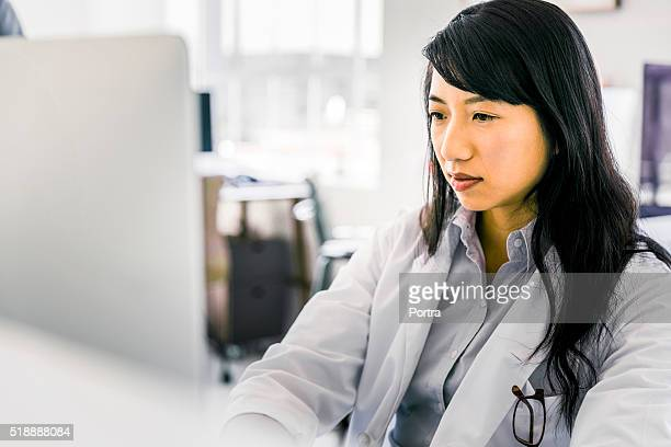 Female doctor using desktop PC
