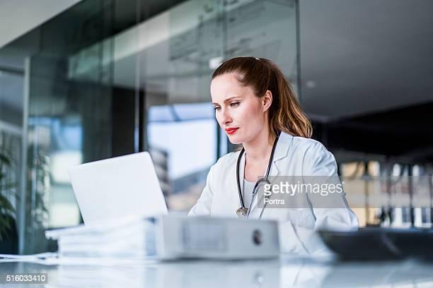 Femme médecin à l'aide d'ordinateur portable dans la clinique