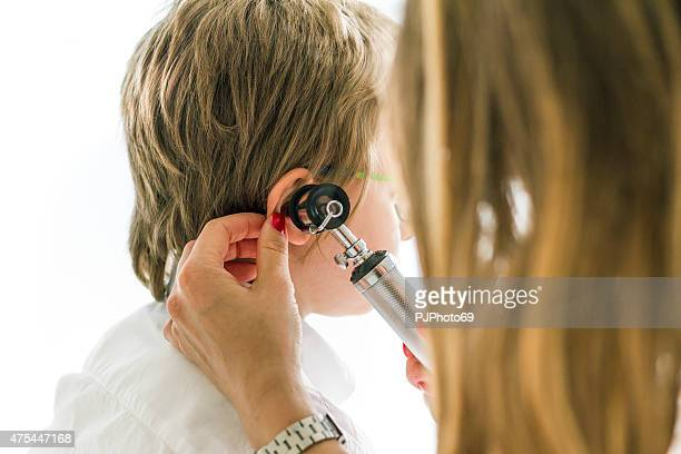 Female doctor using otoscope on child