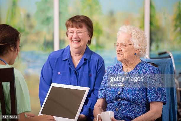 Female doctor visits elderly woman patient in nursing home. Laptop.