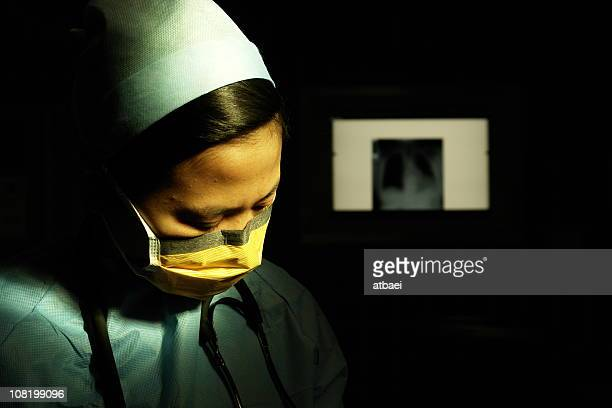 Female Doctor Wearing Scrubs and Mask with X-ray in Background