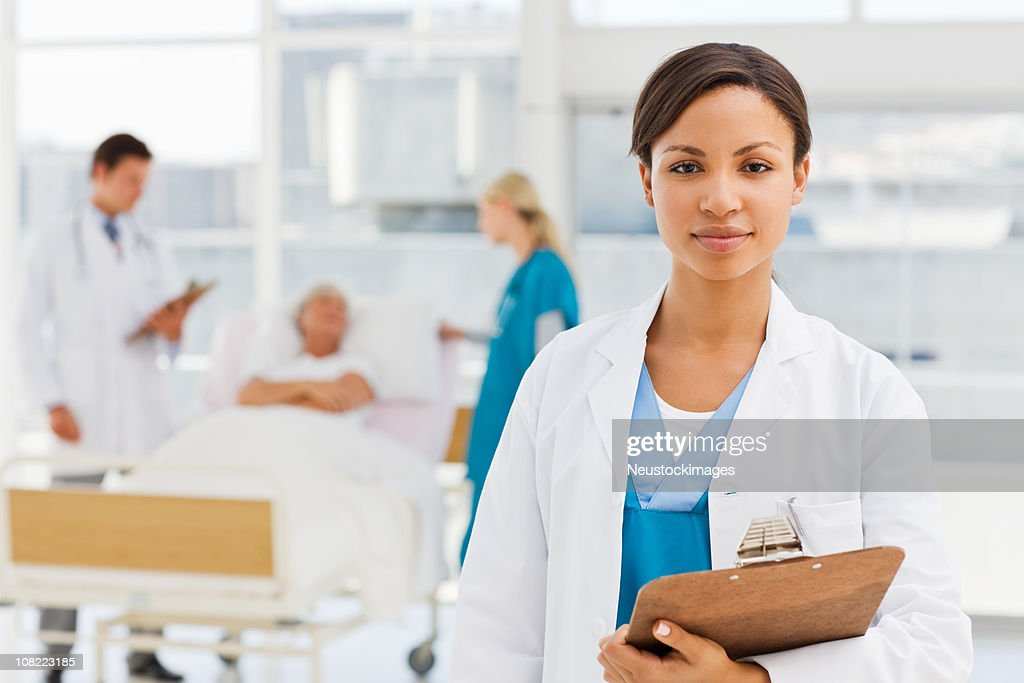 Female doctor with colleagues and patient in background : Stock Photo