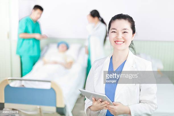 Female doctor with colleagues and patient in background