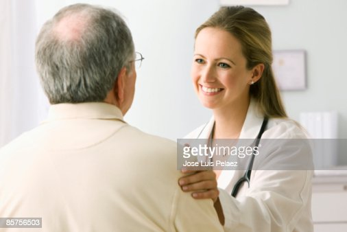 Female doctor with hand on male patient's arm : Stock Photo
