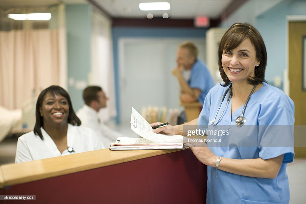 Female doctor with receptionist in hospital, smiling, portrait : Stock Photo