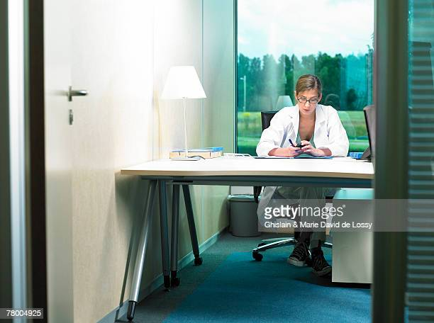 Female doctor working at her desk. View from opened door.