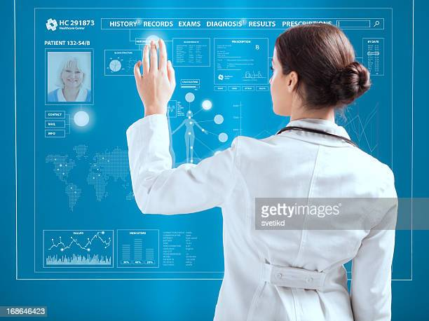 Female doctor working on transparent monitor.